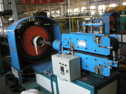 A machine is wrapping water clothes on hydraulic hose.